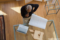 A black architect holding a pencil and working with his laptop, blueprints and a model on a glass table top. The camera is above looking down. The architect has short gray hair and is standing on a hardwood floor.